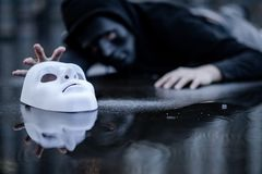 Mystery hoodie man trying to grab white mask. Mystery hoodie man in black mask lying in the rain trying to grab white mask on wet floor. Major depressive royalty free stock image