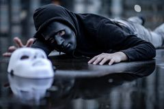 Mystery hoodie man in broken black mask lying in the rain trying to grab white mask on wet floor. Major depressive disorder or. Bipolar disorder. Depression stock image