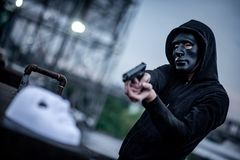 Mystery hoodie man in broken black mask pointing gun at white mask. Crime and violence concepts. Mystery hoodie man in broken black mask pointing gun at white stock photo