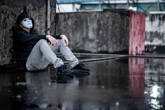 Mystery hoodie man in white mask sitting in the rain looking up at the sky on rooftop of abandoned building. Bipolar disorder or. Major depressive disorder stock photos