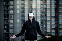 Mystery hoodie man in white mask standing in the rain looking up at the sky on rooftop of abandoned building. Bipolar disorder or. Major depressive disorder stock images
