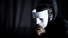 Mystery man in black mask holding white mask royalty free stock image