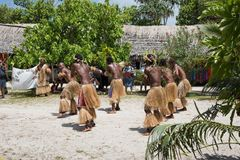 Mystery Island Dancers. MYSTERY ISLAND, VANUATU, PACIFIC ISLANDS: DECEMBER 2,2016: Performance dance group, thatched roof structure, tourists, and tropical flora Royalty Free Stock Image