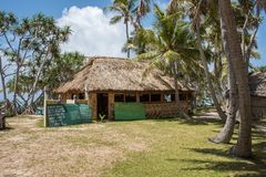 Mystery Island Hut and Signage. MYSTERY ISLAND, VANUATU, PACIFIC ISLANDS: DECEMBER 2,2016: Thatched roof structure with signs, and tropical flora on Mystery Stock Photography