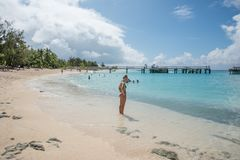 Mystery Island: Recreation in Paradise. MYSTERY ISLAND, VANUATU, PACIFIC ISLANDS-DECEMBER 2,2016: Young adult standing on beach edge with tourists swimming in Royalty Free Stock Photography