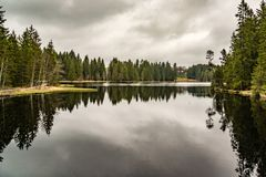 Mystery lake with forest, dark water reflection. Cloudy Stock Photo