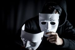 Mystery man in black mask holding white masks royalty free stock images