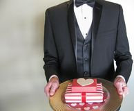 Mystery man in black tuxedo with Valentine's Day gifts. Elegantly dressed male holding red and white gift- wrapped valentine presents on a gold tray Royalty Free Stock Photo