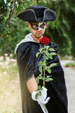 Mystery man holding a rose. Mystery man in black mask and velvet cape holding a red rose. Selective focus Royalty Free Stock Photos