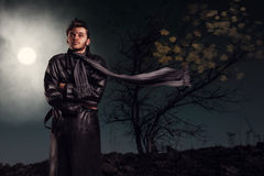 Mystery man under the moonlight. Portrait of handsome no fear man in leather jacket with long scarf standing in the strong wind under the moonlight. Midnight stock photography