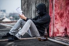 Mystery man in black mask looking at white mask on his hand. Mystery man wearing black mask and hoody jacket looking at white mask on his hand, depression self Stock Photography