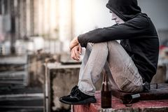 Mystery man in the mask sitting with empty and broken bottle. Mystery man in the white mask with hoody jacket, sitting with empty and broken bottle in abandoned stock image