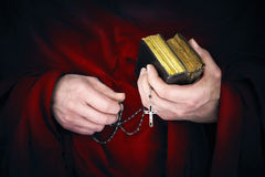 Mystery monk with a cape holding bibles and a black rosary stock photography