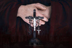 Mystery monk's hands with a cape, crucifix and a black rosary Stock Image