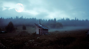 The mystery moon. Little house over the mystery moon landscape Royalty Free Stock Photo