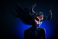 Mystery portrait of female faun. With blue eyes, body art and silver snakes on black horns Royalty Free Stock Image