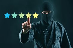 Mystery shopper or review online concept. Rating online. 5 stars review and ninja in mask on a dark background.  royalty free stock images