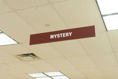 Mystery sign. A sign hanging from a library ceiling indicates the mystery section Stock Photography