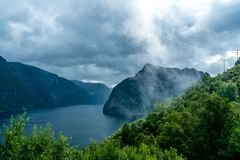 Mystery view onto a fjord with fog and clouds royalty free stock photo