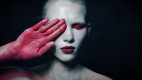 Mystery weird girl close half of her face with bloody hand. Horror and mystic concept stock footage