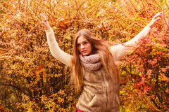 Mystery woman against autumnal leaves outdoor. Beautiful autumn season. Fashionable mystery woman posing against colorful autumnal leaves outdoor in park Stock Images