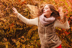 Mystery woman against autumnal leaves outdoor. Beautiful autumn season. Fashionable mystery woman posing against colorful autumnal leaves outdoor in park Royalty Free Stock Image