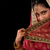 Mystery young Indian female. Portrait of beautiful mystery young Indian woman covering her face by veil, looking at camera, copy space at side, isolated on black Royalty Free Stock Images
