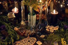 Alchemy still life with glass bottles and flask, runes, healing herbs and ritual objects. Mystic background with ritual esoteric objects, occult, fortune telling stock photo