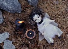 Scary still life with voodoo girl and black candles. Mystic background with ritual esoteric objects, occult and halloween scary concept stock image