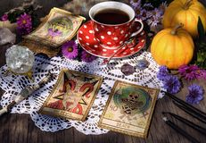 Still life with cup of tea, pumpkins, crystal, black candles and tarot cards on lace royalty free stock images