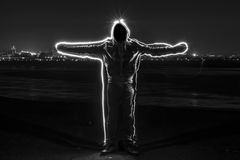 Mystic black hooded man standing in the darkness. Stock Images