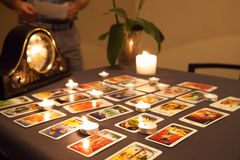 Mystic fortune-telling with fired candles and playing cards in d. Ark on background stock photography