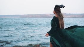 Mystic lady with long hair in flying gorgeous green dress, witch in emerald velor gown on shore of magical lake, girl