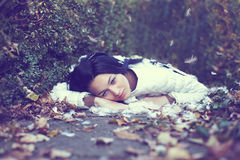 Mystic lonely angel girl lying on the ground. Among the fallen leaves and feathers Stock Image