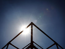 Mystic Pyramid. An abstract tubular pyramid with a sun ray bursting from behind the metal frame on a blue surreal sky royalty free stock images