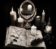 Mystic still life with black magic book, candles and mirrow. Mystic still life with old book, runes, candles and mirror in grunge retro style. Halloween concept stock images