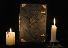 Mystic still life with black magic book and two burning candles Stock Image