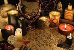 Mystic still life with demon manuscript, mirror and black candles. Halloween concept. Esoteric objects on table. There is no foreign text in the image, all stock photography