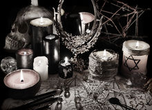 Mystic still life with magic mirror, demon paper and candles in grunge vintage style. Esoteric objects on table. There is no foreign text in the image, all stock images