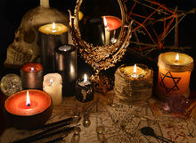 Mystic still life with magic mirror, demon paper and candles. Halloween concept. Esoteric objects on table. There is no foreign text in the image, all symbols royalty free stock photos