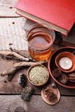 Authentic interior details, glass of herbal rea, dry herbal plants, homeopathic treatment on rustic wooden background, alternative stock photo