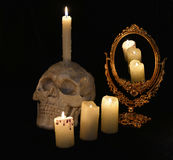 Mystic still life with skull, mirrow and burning candles. Mystic still life with skull, mirror and burning candles in the darkness. Halloween concept, black stock photography