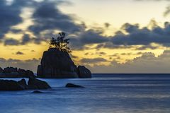 Mystic sunset over rock with single tree. seychelles 2. Mystic sunset over granite rocks in the water with a single tree at baie lazare on the seychelles Royalty Free Stock Photography