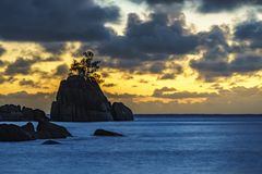 Mystic sunset over rock with single tree. seychelles 4. Mystic sunset over granite rocks in the water with a single tree at baie lazare on the seychelles Stock Images