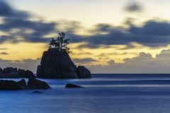 Mystic sunset over rock with single tree. seychelles 1. Mystic sunset over granite rocks in the water with a single tree at baie lazare on the seychelles Royalty Free Stock Photos