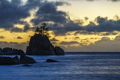 Mystic sunset over rock with single tree. seychelles 3. Mystic sunset over granite rocks in the water with a single tree at baie lazare on the seychelles Royalty Free Stock Photo