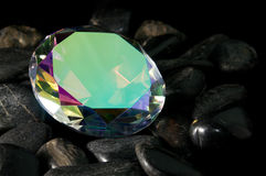 Mystic Topaz Faceted Gemstone. Mystic topaz round cut faceted gemstone sitting on rocks Royalty Free Stock Image