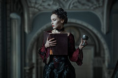 Mystic woman with a book. Mystic woman with book and cup in the Gothic style Stock Photos