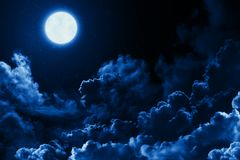 Mystical bright full moon in the midnight sky stars surrounded by dramatic clouds. Dark background twilight night sky
