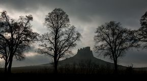 Mystical dark and stormy view of Spissky hrad castle in Slovakia. Mystical dark and stormy view of Spissky hrad castle and a field with bold trees in autumn  in Royalty Free Stock Photos